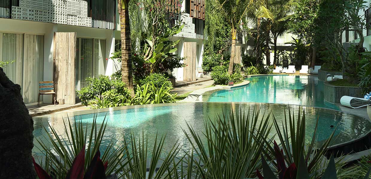 akmani legian pool with shrubs in the foreground and lush trees overhanging the pool