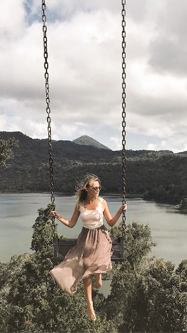 woman with a long flowing dress and sunglasses swinging on the buyan lake swing