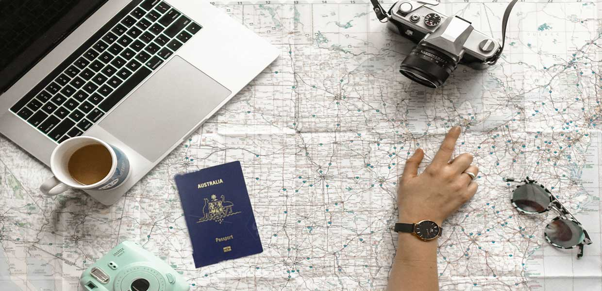 pointing to map with a passport and computer on it