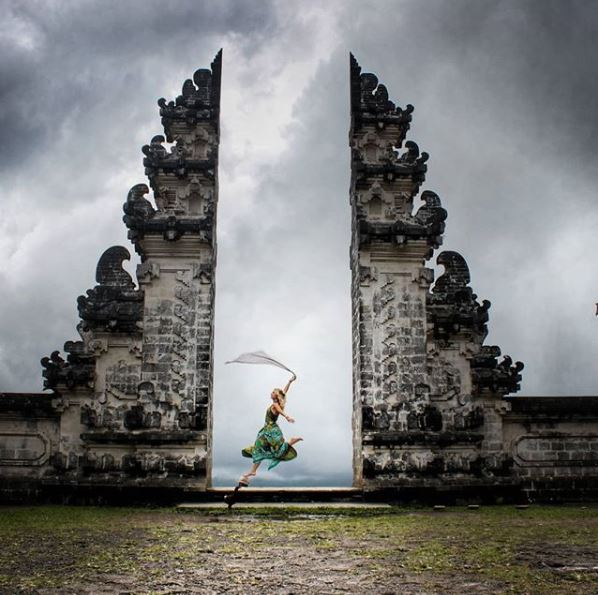 woman dancing with cloth in her hand between gates at pura lempuyang