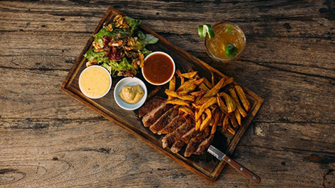 Cut steak and chips neatly arranged on a tray with three sauces and a side of salad