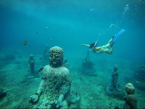 woman in white bikini snorkeling towards statue at pemuterans underwater temple