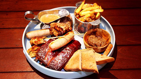 Various meats and chips arranged on plate with gravy for garnish