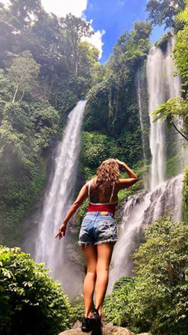 slender woman with dixie shorts and red top looking up to sekumpul waterfalls