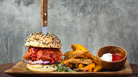 Pulled pork burger with a knife holding it together sided by thick chips and tomato sauce