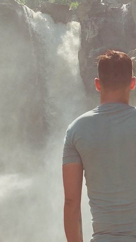 man with short cropped hair and a grey t shirt looking at tegenungan waterfall