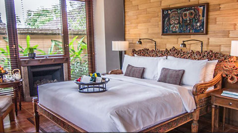 the chedi club bedroom with traditional balinese wood carved bed