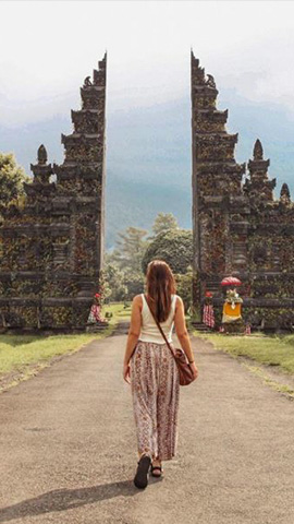 woman with handbag and sandals walking towards gates of ulun danu temple