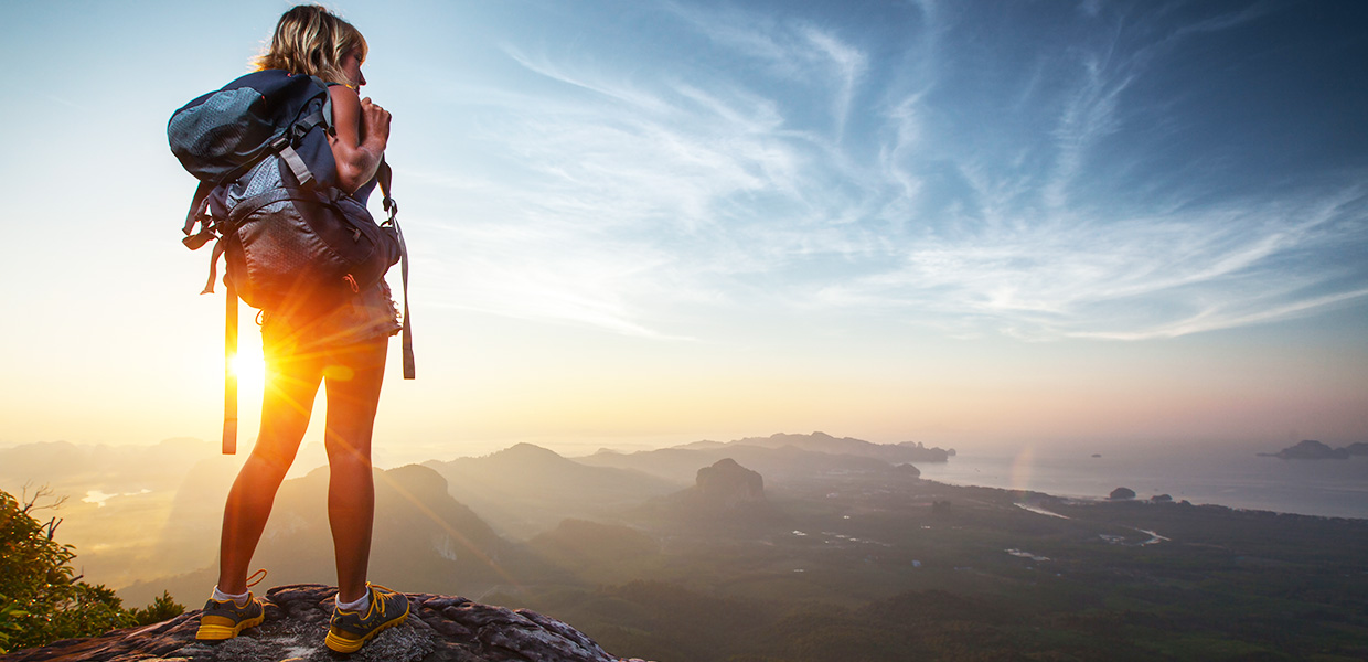 woman wearing a backpack overlooking mountains, packing for bali