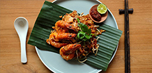 cooked marinated prawns on a bedding of bamboo with sauce and lime